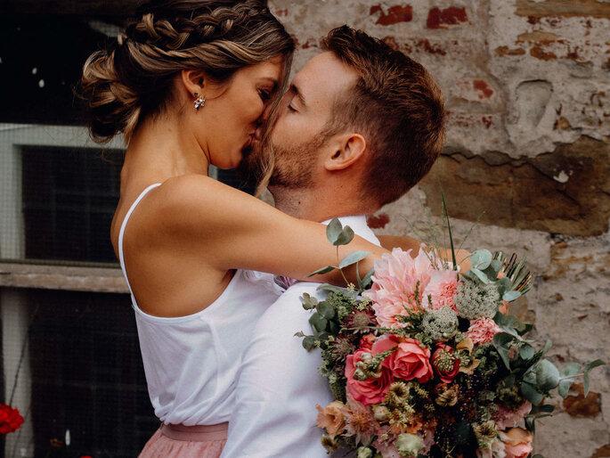 Ein Brautpaar küsst sich leidenschaftlich.