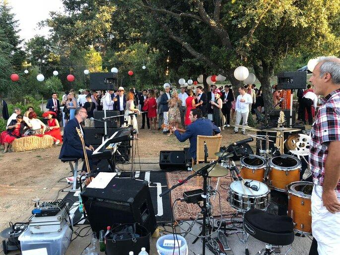 Une fête de mariage avec un orchestre et des animations est organisée en extérieur