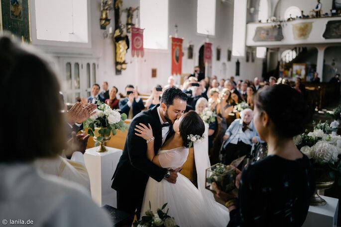 Brautpaar beim Brautkuss nach der Trauung in der Kirche