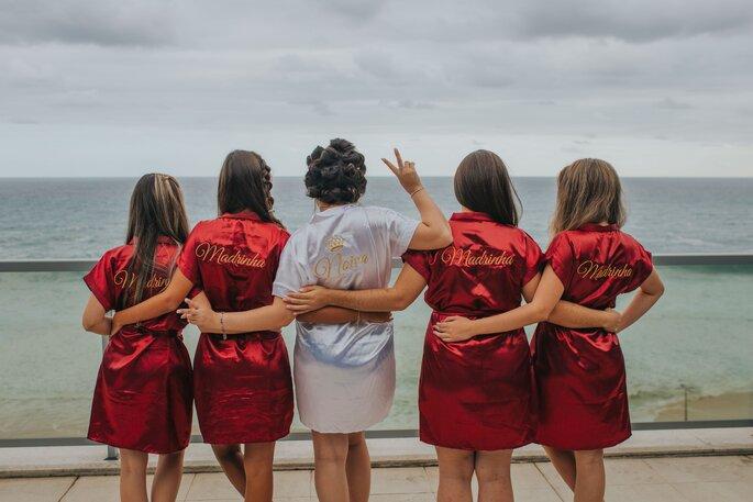 Braut mit Brautjungfern in Bademantel am Strand