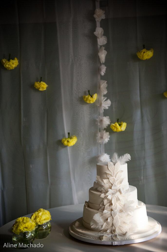 Hermosa torta blanca con detalles de flores y guirnalda amarillas. Foto: Aline Machado