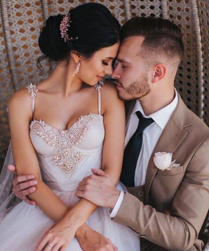 Anges et Rêves - une mariée dans les bras d'un futur marié. Elle porte un bustier brodé de perles et une jupe en tulle.