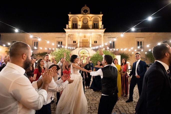 Coppia di neo sposi ballando all'esterno della location italiana