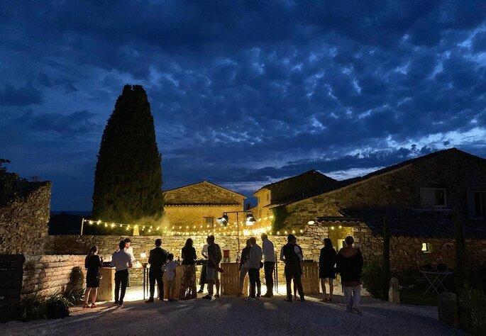 Réception de mariage debout à la nuit tombée, sous des éclairages