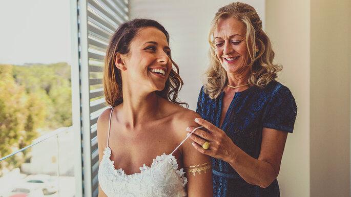 a mãe a ajudar a noiva arranjar-se