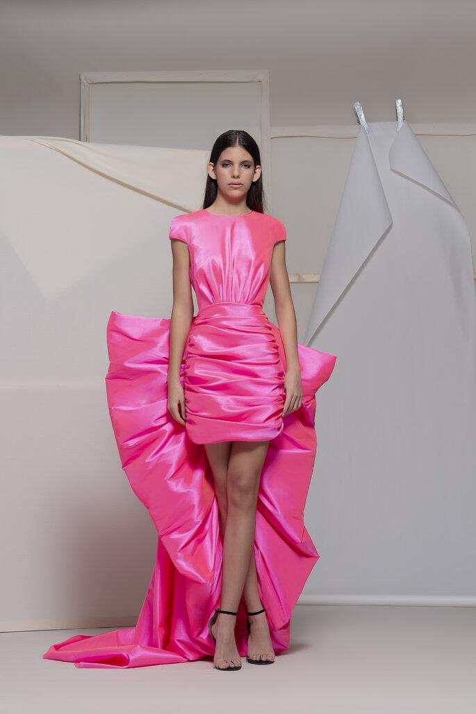 Isabel Sanchis Colección Primavera Verano 2020 - 2021, vestido corto de fiesta rosa fosforescente con adorno de moño gigante en la parte de atrás de la falda plisada.