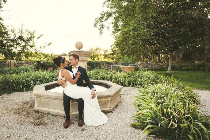 Couple de mariés enlacés assis sur le rebord d'une fontaine dans un superbe parc arboré