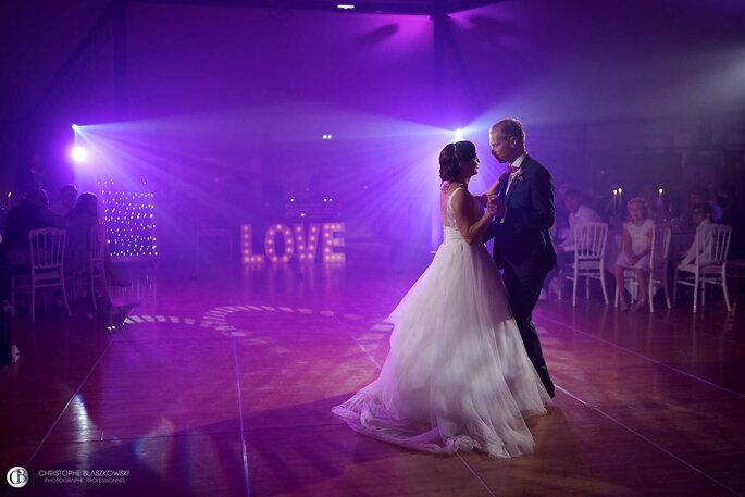 Un couple de mariés entamant leur première danse dans une ambiance tamisée et romantique.