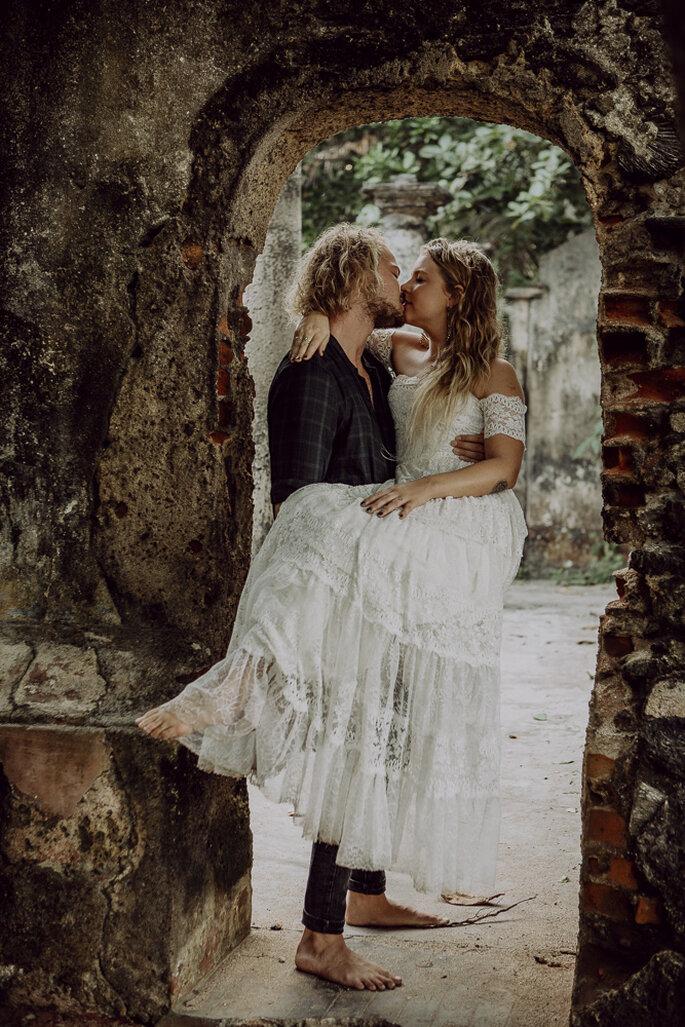 Der Bräutigam trägt die Braut über die Schwelle und küsst sie dabei.