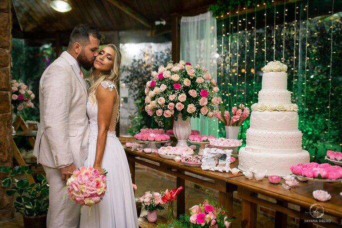 Casal posa em frente à mesa de bolo e doces