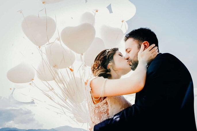 Pareja de esposos besándose con fondo de globos blancos