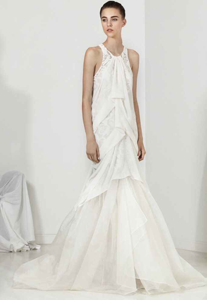 Vestido largo de novia con volumen en las telas, detalles de encaje y hombros descubiertos