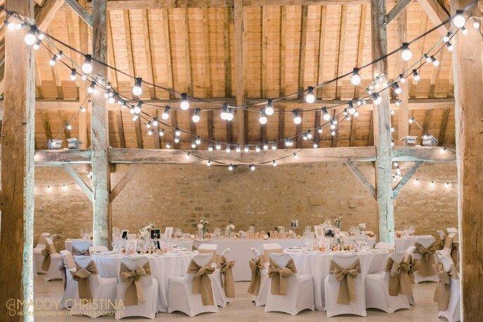Des tables sont dressées pour un mariage, sous une charpente aux poutres apparentes illuminée de lampions.