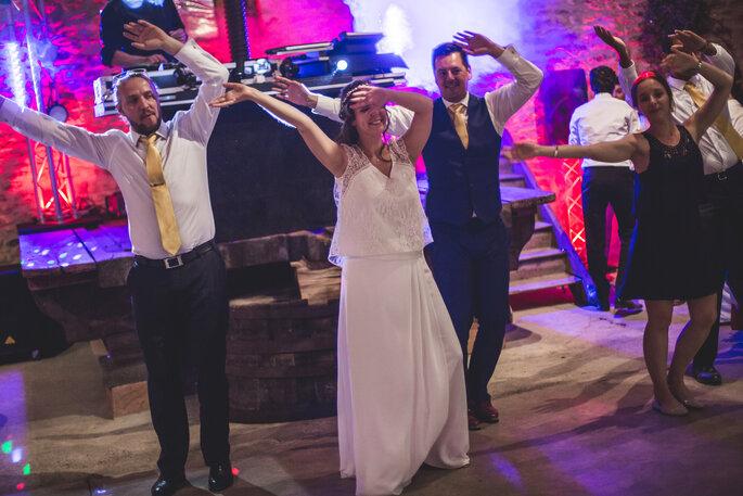 Un couple de mariés et leurs proches en train de danser pendant la soirée du mariage