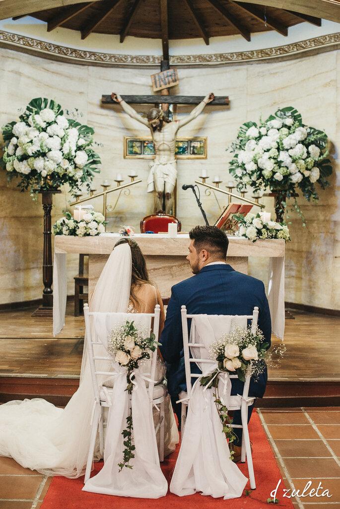 Novios sentados frente al altar