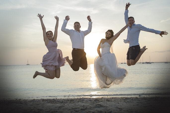 Ein Brautpaar und ihre Gäste springen am Strand in die Luft.