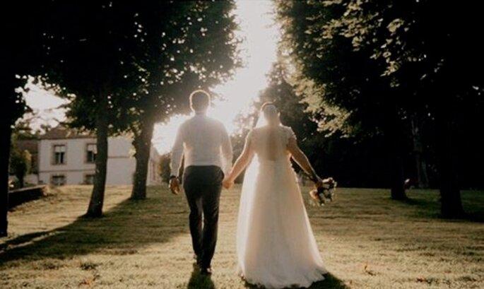 Un couple de mariés qui se tient la main avance dans une allée bordée par des arbres.