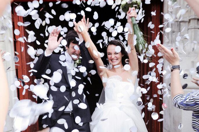 Des mariés sortent de l'église sous un lancer de pétales de fleurs