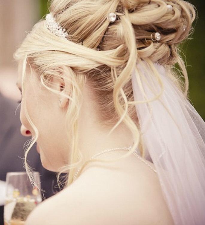 Los trenzados combinados con mechones sueltos y accesorios brillantes también pueden combinarse con el velo. Foto: www.yourphoto.de