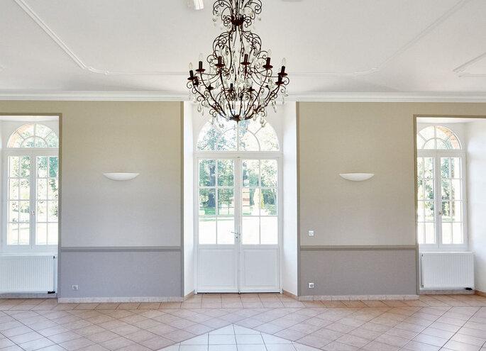 Salle de réception vide avec de grandes fenêtres donnant sur le parc, un bel espace à décorer, aménager ou en guise de piste de danse et un gros lustre en fer forgé