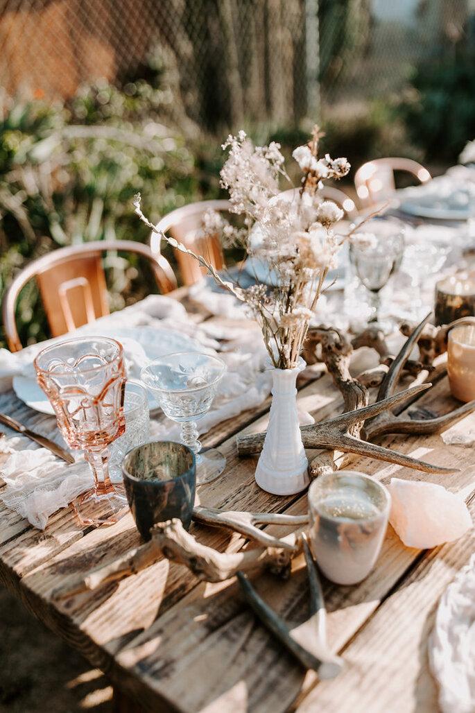 Decoración para mesa con pequeños troncos y floreros blancos con naturaleza muerta.