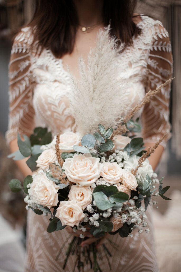 Eine Braut mit einem Spitzenbrautkleid. Sie trägt einen opulenten Brautstrauß in den Händen.