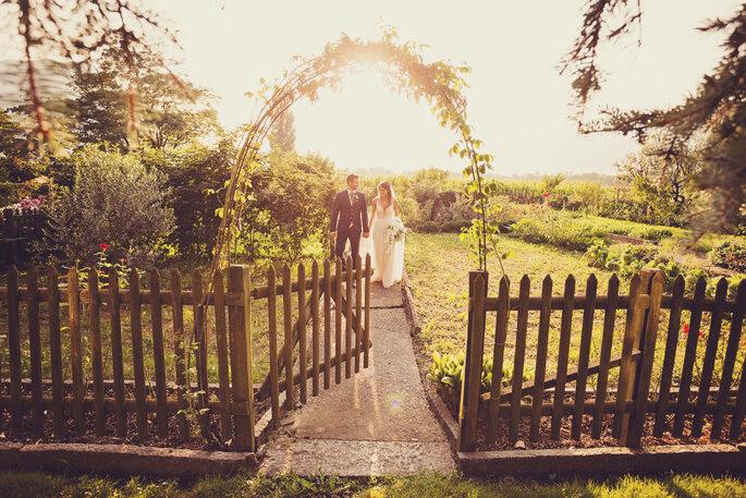 Hochzeitsfoto. Brautpaar vor Sonnenuntergang hinter Gartentürchen