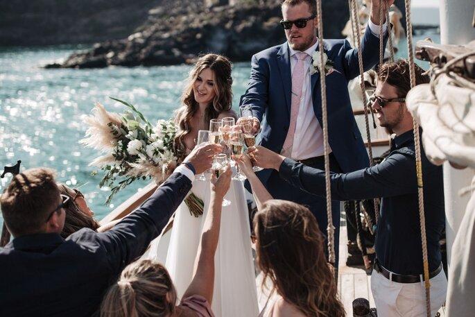 Ein Brautpaar stösst mit seinen Gästen an.