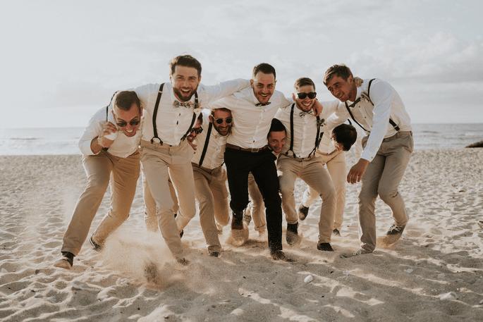 Le marié et ses amis se rassemblent sur la plage