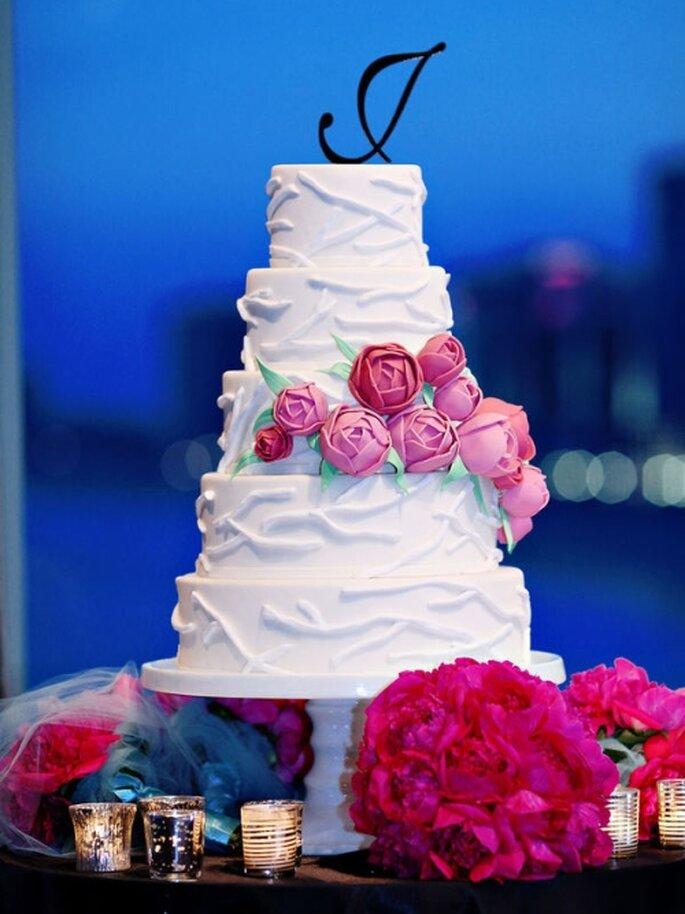 Gâteau de mariage blanc avec quelques roses. Photo: Style Me Pretty
