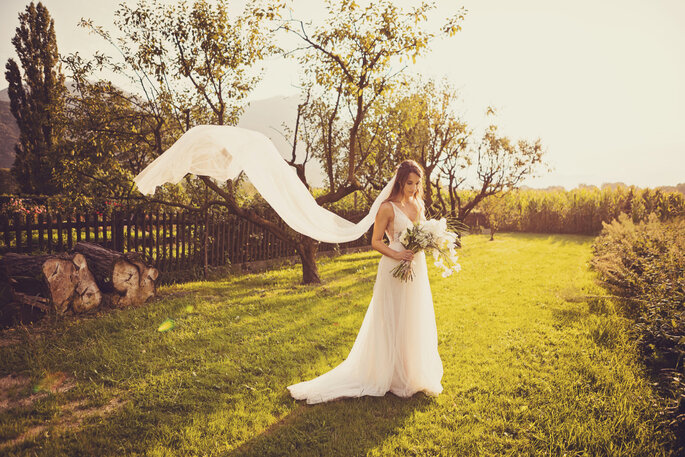 Hochzeitsfoto. Braut im Garten mit fliegendem Schleier