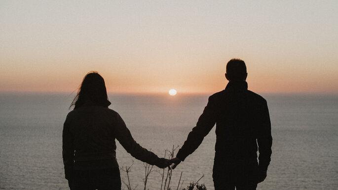 Brautpaar Händchen haltend mit Blick aufs Meer