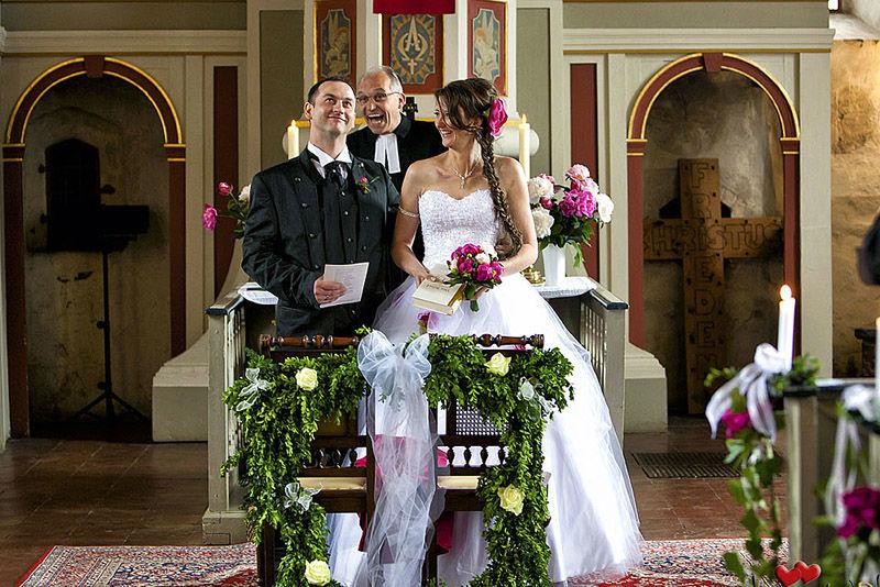 Beispiel: Fotos von der Trauzeremonie, Foto: Hochzeitsfotografie Iris Woldt.lachender Pfarrer bei der Trauung