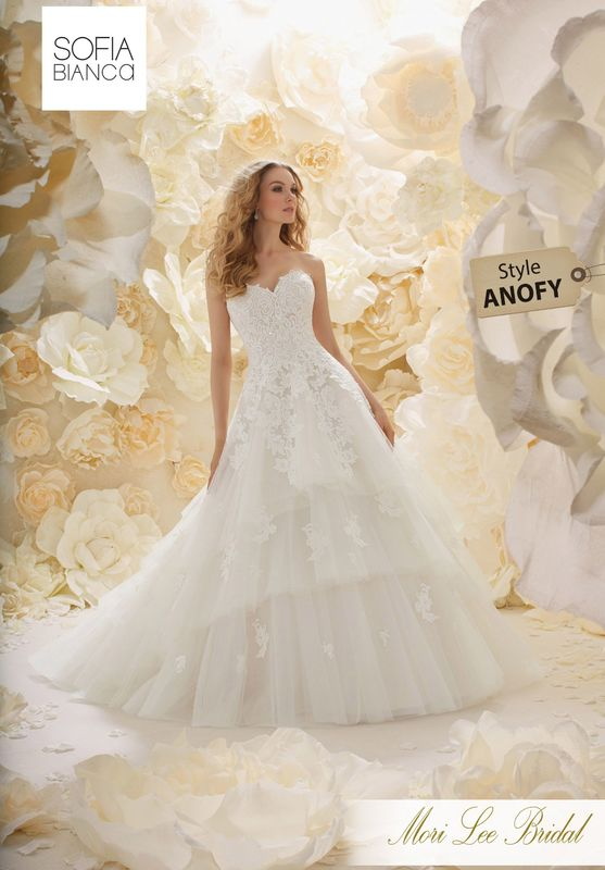 Style ANOFY A STRAPLESS LACE BODICE ON A LAYERED TULLE SKIRT WITH EMBROIDERED LACE APPLIQUES DETAIL AVAILABLE IN 3 LENGTHS: 55', 58' AND 61'     COLOURS WHITE, IVORY, IVORY / CHAMPAGNE