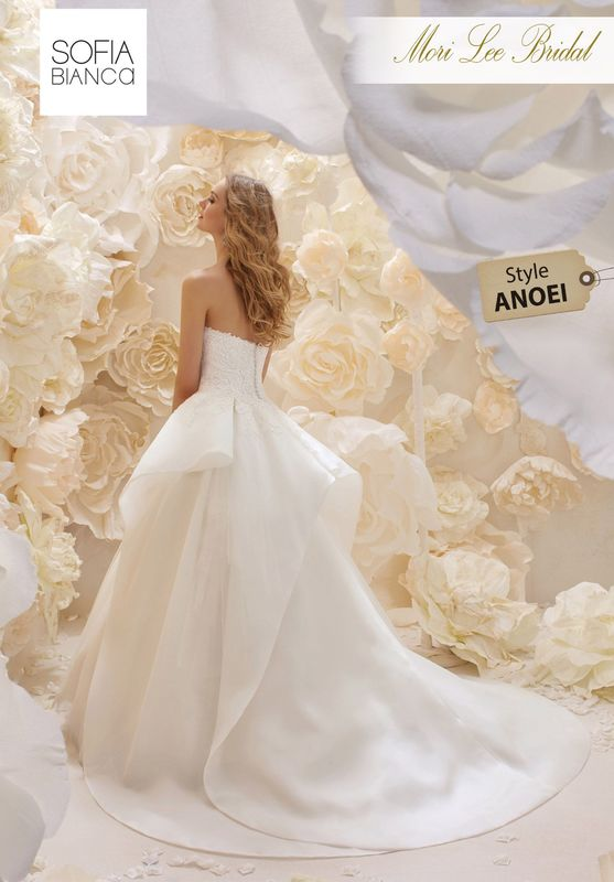 Style ANOEI A STRAPLESS ORGANZA BODICE WITH LACE APPLIQUES ON A FULL TULLE SKIRT WITH ASYMMETRIC OVERLAY CREATING DISTINCT SHAPE AND A UNIQUE TRAIN   COLOURS WHITE OR IVORY