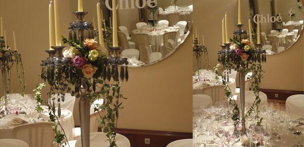 Candelabros de estilo frances con una composición floral en tonos rosas., y cristales fumé.  http://lafloreria.net