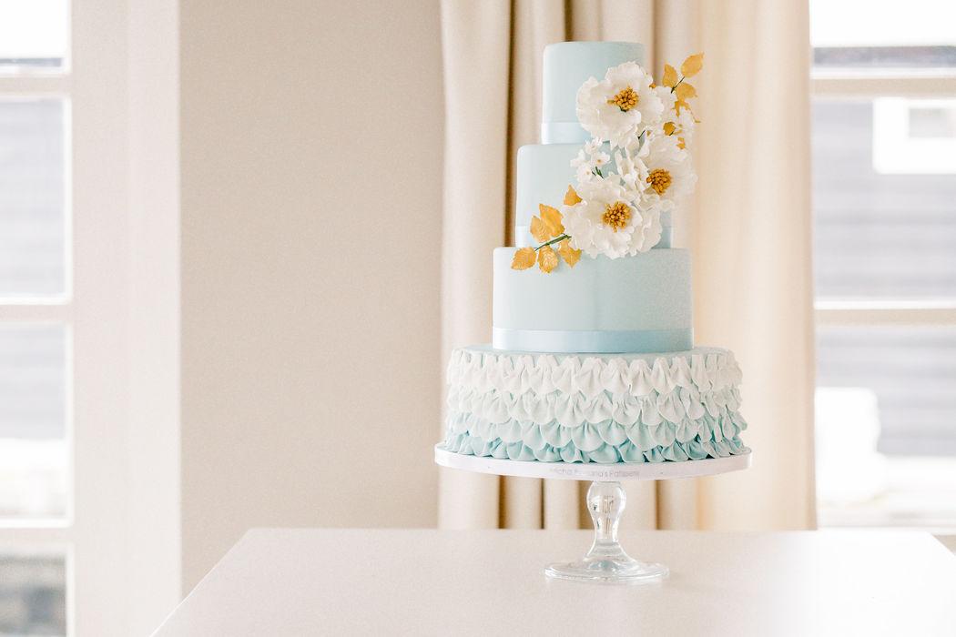Bruidstaart bestaande uit vier lagen met handgemaakte bloemen.