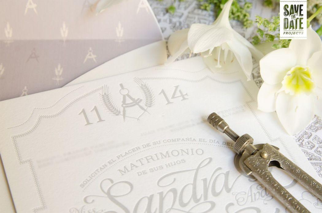 Detalle Logo - Invitación vintage impresa en letterpress (impresión con relieve), sobre un papel de 450 gr. Incluye el logo de los novios (compás = Arquitectura + Espiga= Agrónomos) y los lugares favoritos de sus viajes.