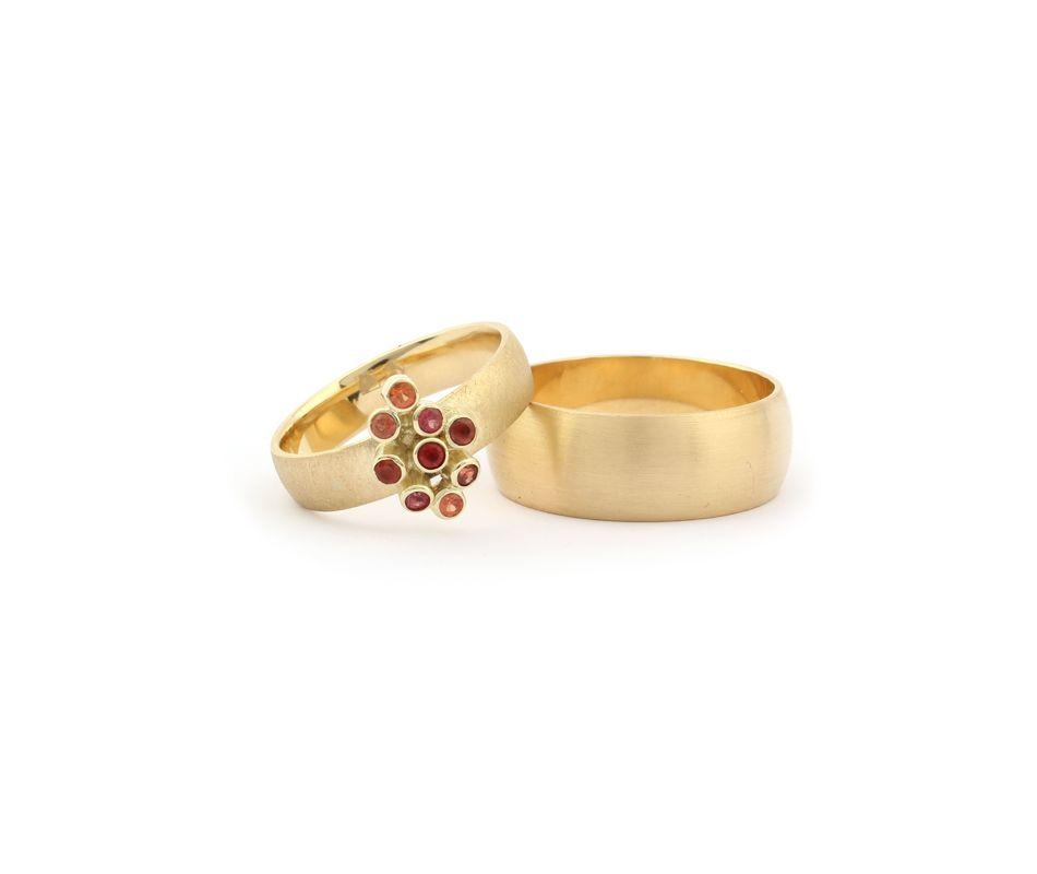Trouwringen van geelgoud met een cluster van rode edelsteentjes. Kan ook gemaakt worden met andere edelstenen.