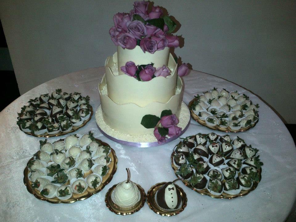 Decoración de mesa de ponqué con pareja de peras, y fresas decoradas de novio y novia con chocolate.