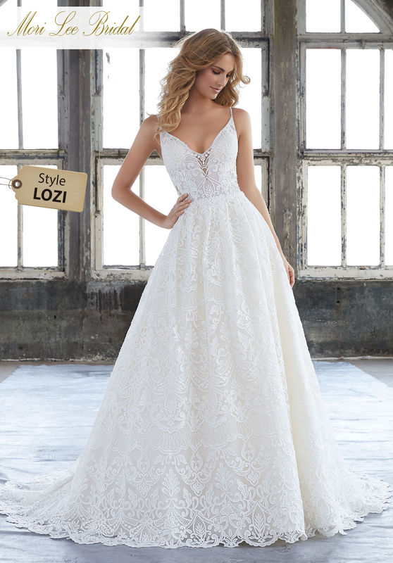 Style LOZI  Kasey Wedding Dress  Vintage Inspired A-Line Bridal Gown Featuring Allover Embroidery on Net. Delicate Beaded Trims the Shoulder Straps and Edge the Illusion V-Back. Matching Satin Bodice Lining Included. Available in Three Lengths: 55″, 58″, 61″. Colors Available: White, Ivory, Ivory/Champagne