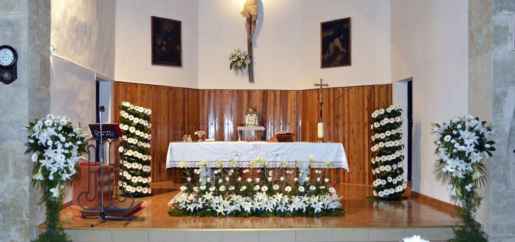 Decoración para boda con columnas de flores y centro en para lelo en la mesa del altar.