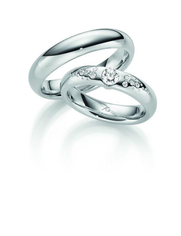 Een smallere witgouden trouwring maar met een bolle binnenkant voor een heerlijk draagcomfort. De damesring is weer speel bezet met diamanten.