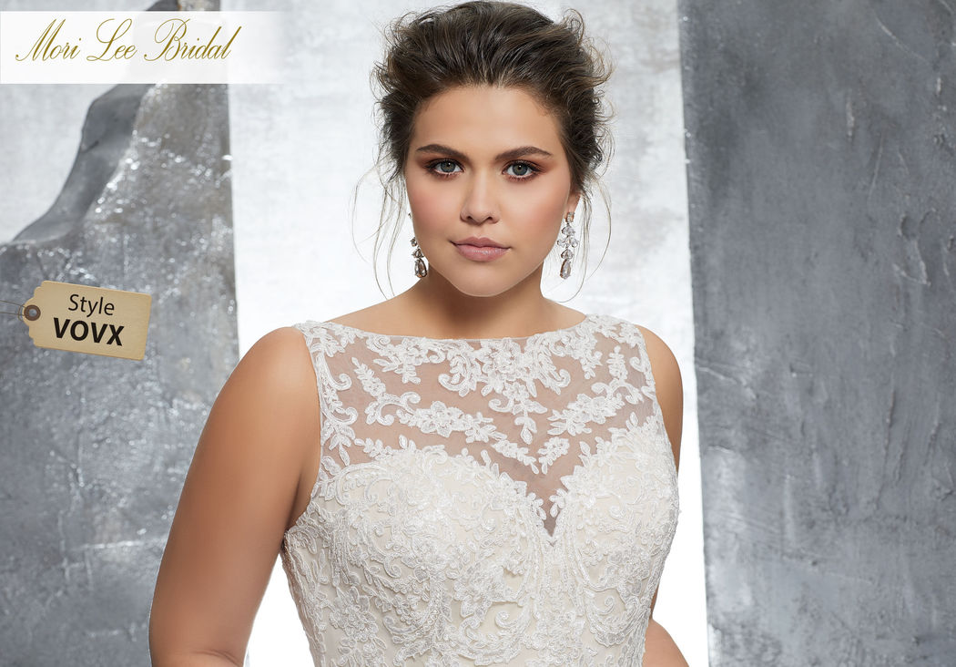 Style VOVX Keri Wedding Dress  Form Fitting Wedding Dress Featuring Frosted Alençon Lace Appliqués on Net with a Scalloped Hemline. A Beautiful Sheer Back Trimmed in Covered Buttons Completes the Look. Available in Three Lengths: 55″, 58″, 61″. Colors Available: White, Ivory, Ivory/ Coco