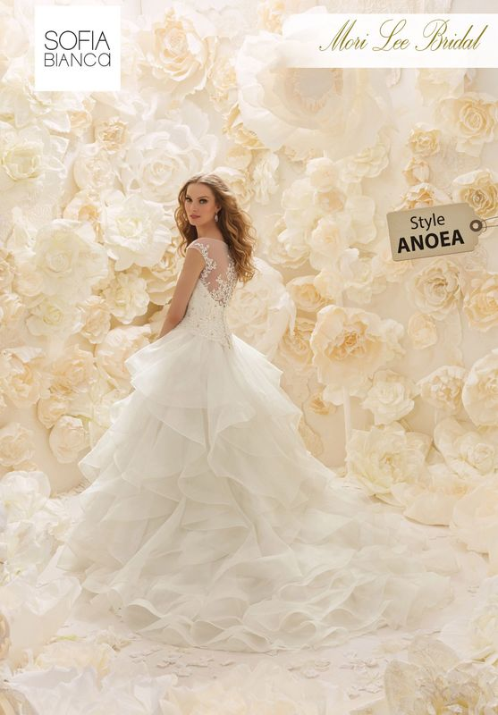 Style ANOEA A BONED CRYSTAL BEADED BODICE WITH ILLUSION DETAIL AND LACE APPLIQUES MEETS A FLOUNCED, RUFFLED ORGANZA SKIRT   AVAILABLE IN 3 LENGTHS: 55', 58' AND 61'     COLOURS WHITE OR IVORY