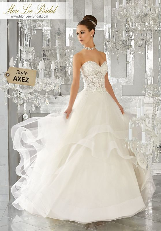 Style AXEZ Mindy Wedding Dress  Intricate Re-Embroidered Lace Appliqués with Crystal Beading Accent the Sheer Sweetheart Bodice on This Flounced Tulle Ball Gown. Matching Satin Bodice Lining Included. Available in Three Lengths: 55″, 58″, 61″. Colors Available: White, Ivory, Ivory/Light Gold.