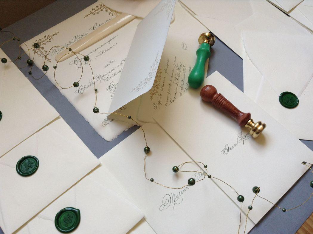 Il Calligrafo - Inviti carta a mano Amalfi con intaglio laser su base color avorio, formato a libro con busta a sacchetto, manoscritti in verde con sigillo verde.