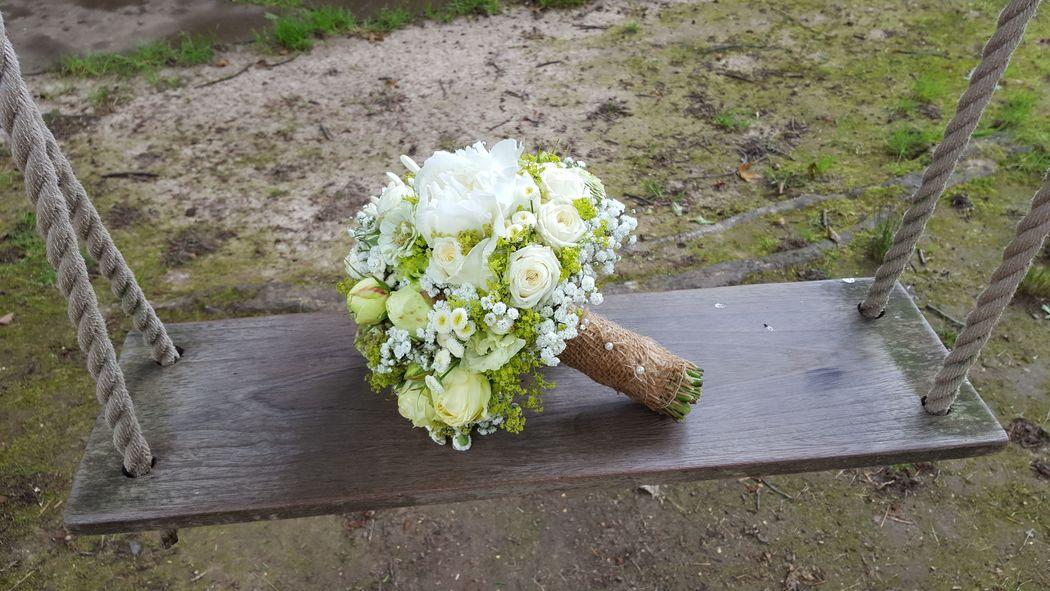 Eine Blütenkugel in weiß/creme zu einer zarten Braut mit passender Deko.