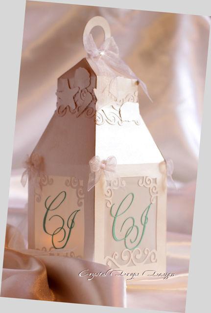 Lanterna in carta perlescente e traslucida. Con iniziali degli sposi in carta perlescente Tiffany. Rifinita con fiocchi in organza, applicazioni intagliate e Swarovski nel fiocco centrale