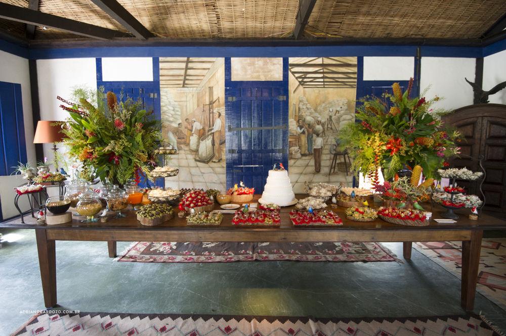 A linda mesa de doces recebeu incríveis arranjos florais, Nas compotas diversos doces típicos